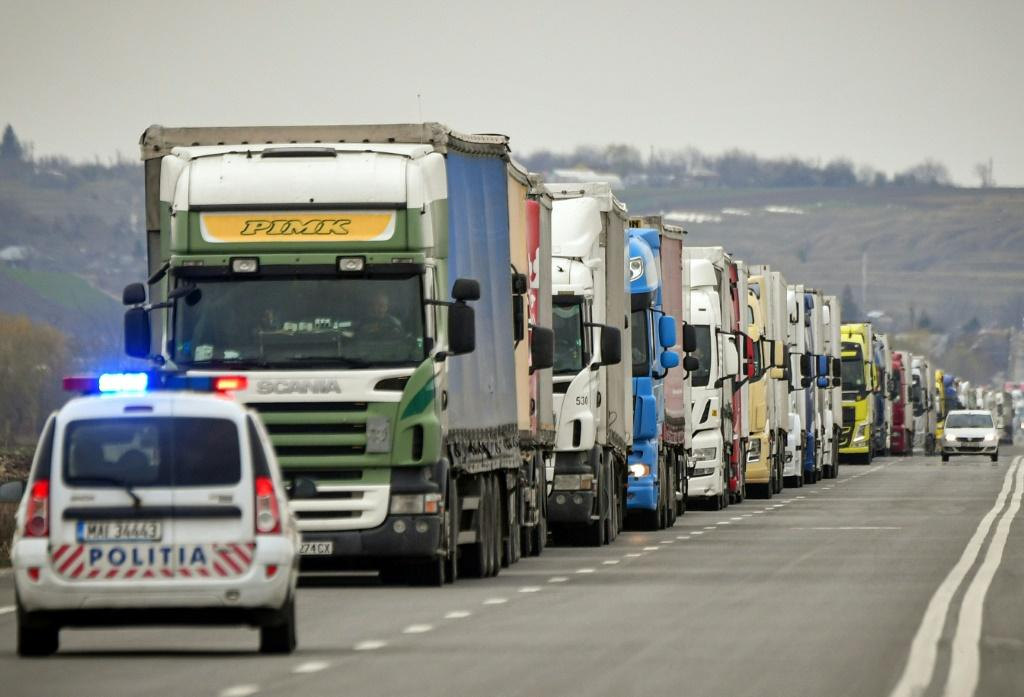 A police car stops delivery trucks for a virus check at the Giurgiu-Ruse border point between Romania and Bulgaria