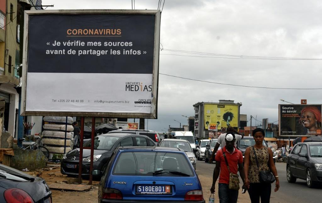 A sign in Abidjan reads 'Coronavirus - I check my sources before sharing news' to warn people against fake news and misinformation about the virus