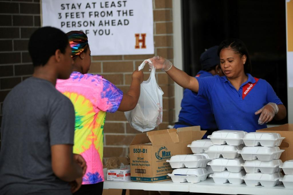 A worker hands out food at Paul Habans Charter School in New Orleans