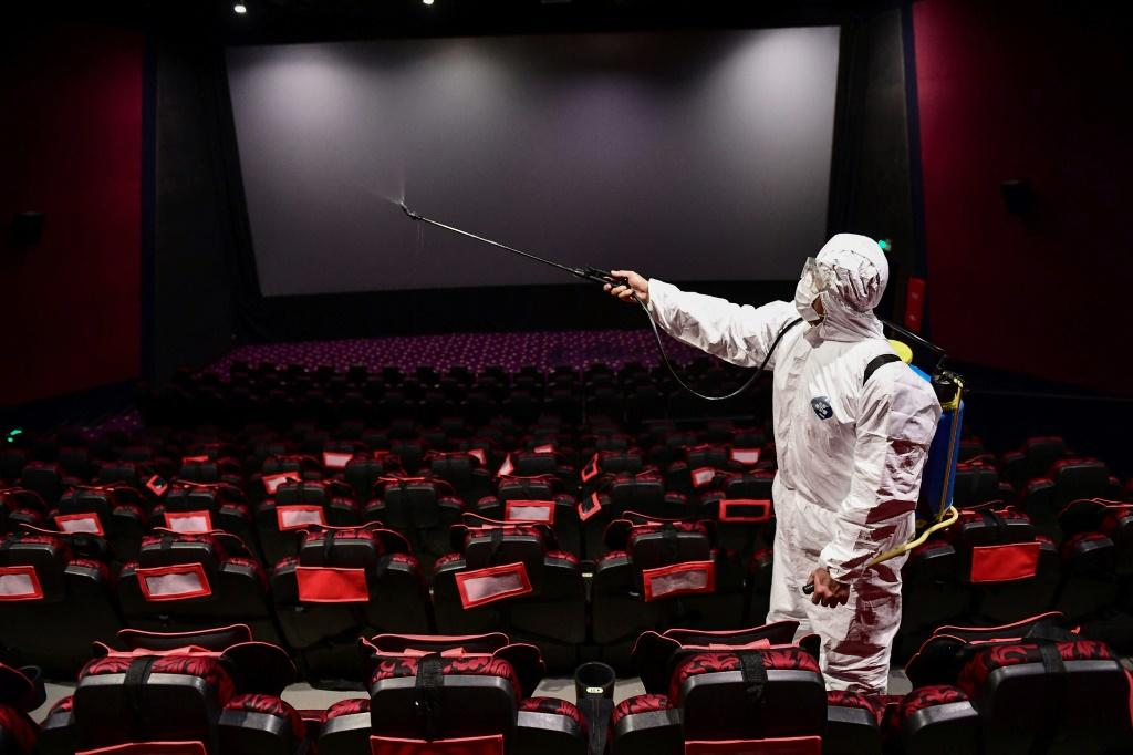 A worker sprays disinfectant in a cinema in the northeastern Chinese city of Shenyang