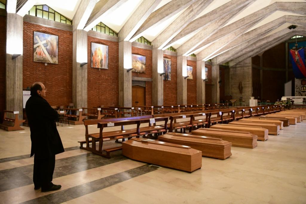 A priest stands by coffins stored in the church of San Giuseppe near Bergamo, Italy