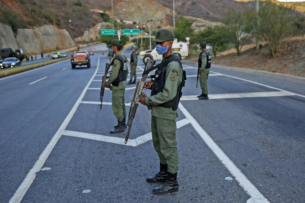 Members of the Bolivarian National Guard partially block road access to the Venezuelan capital, in Caracas -- President Nicolas Maduro retains support of the powerful military