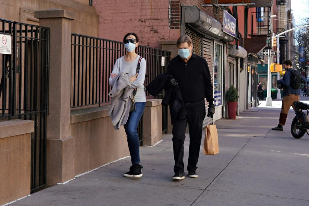 Two people wearing protective masks walk on New York City's Upper East Side as the coronavirus continues to spread