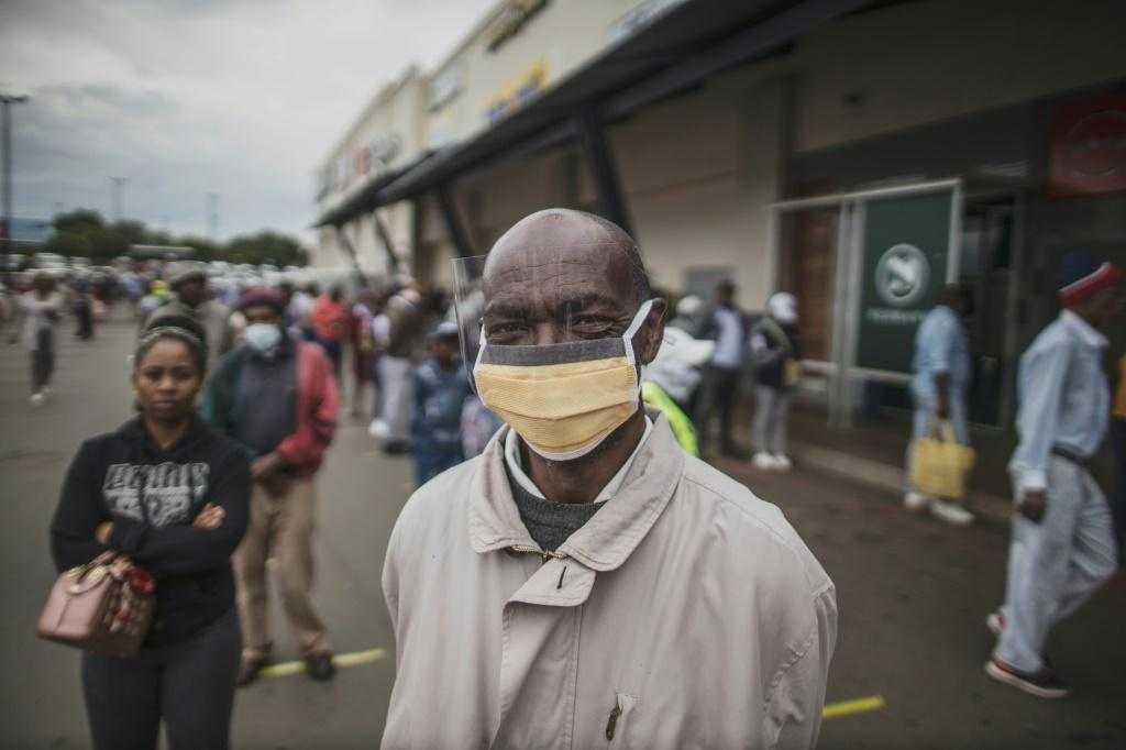Masked: An elderly man in the Johannesburg suburb of Soweto waits in line at a pay point operated by South Africa's Social Security Agency