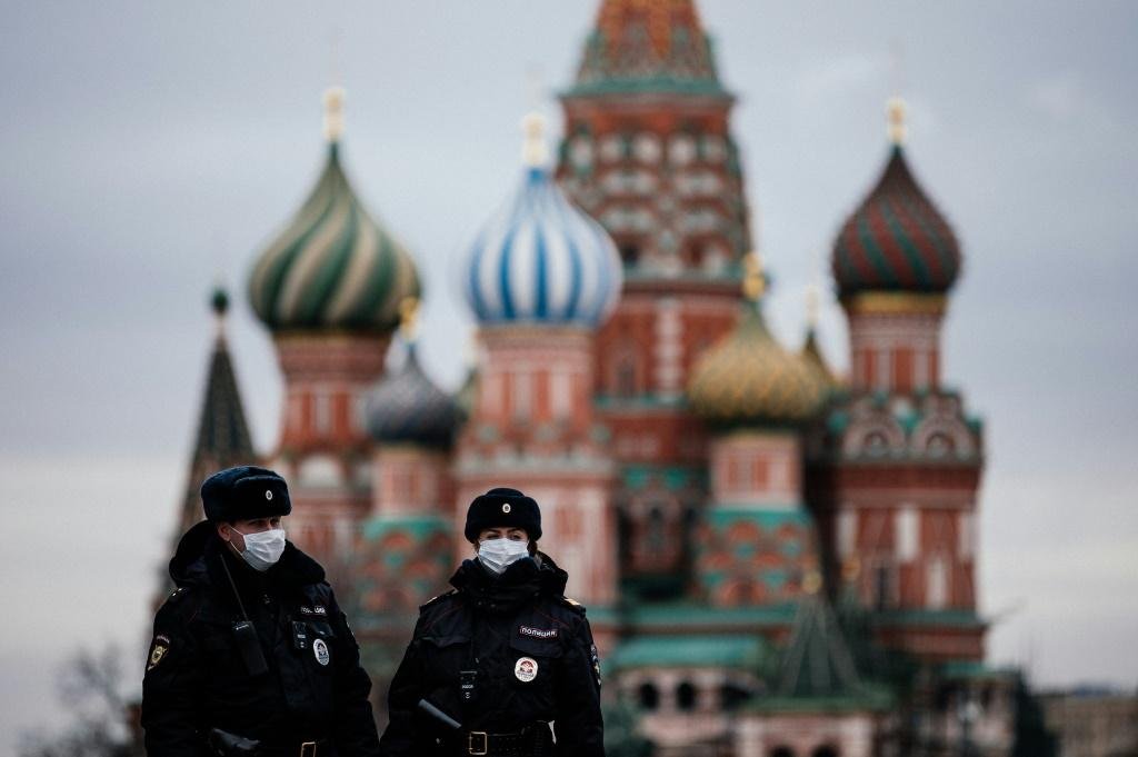 Russian police officers patrol a deserted Red square in front of Saint Basil's Cathedral in Moscow as the capital and other parts of Russia go into lockdown to curb the novel coronavirus.