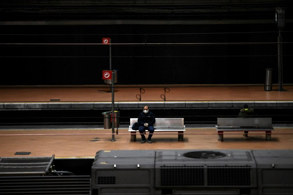 A man wearing a face mask sits on a bench on a platform of Atocha railway station in Madrid during the national lockdown