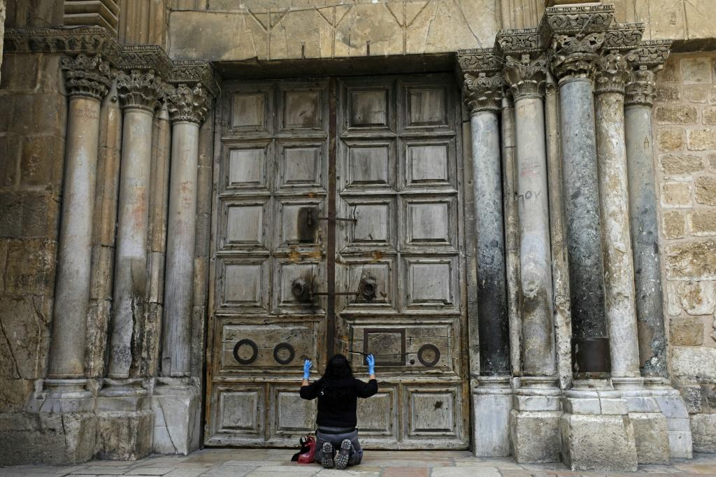 A woman prays in front of the doors of Church of the Holy Sepulchre in the Old City of Jerusalem following its closure due to the coronavirus