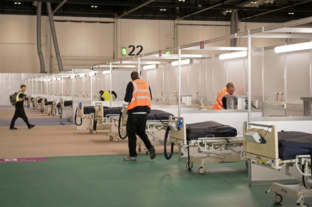 Members of the military and private contractors help to turn the ExCel centre in London into a field hospital to be known as the NHS Nightingale, to help with the COVID-19 pandemic