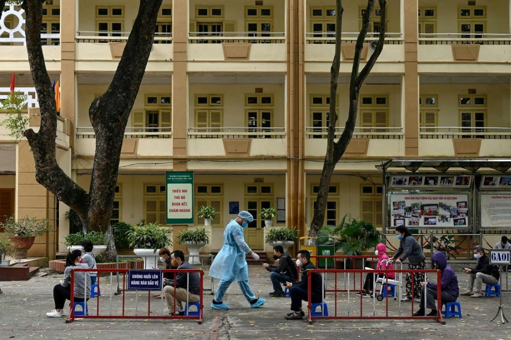Residents wearing face masks practise social distancing as they wait to be tested at a makeshift rapid testing centre in Hanoi, Vietnam