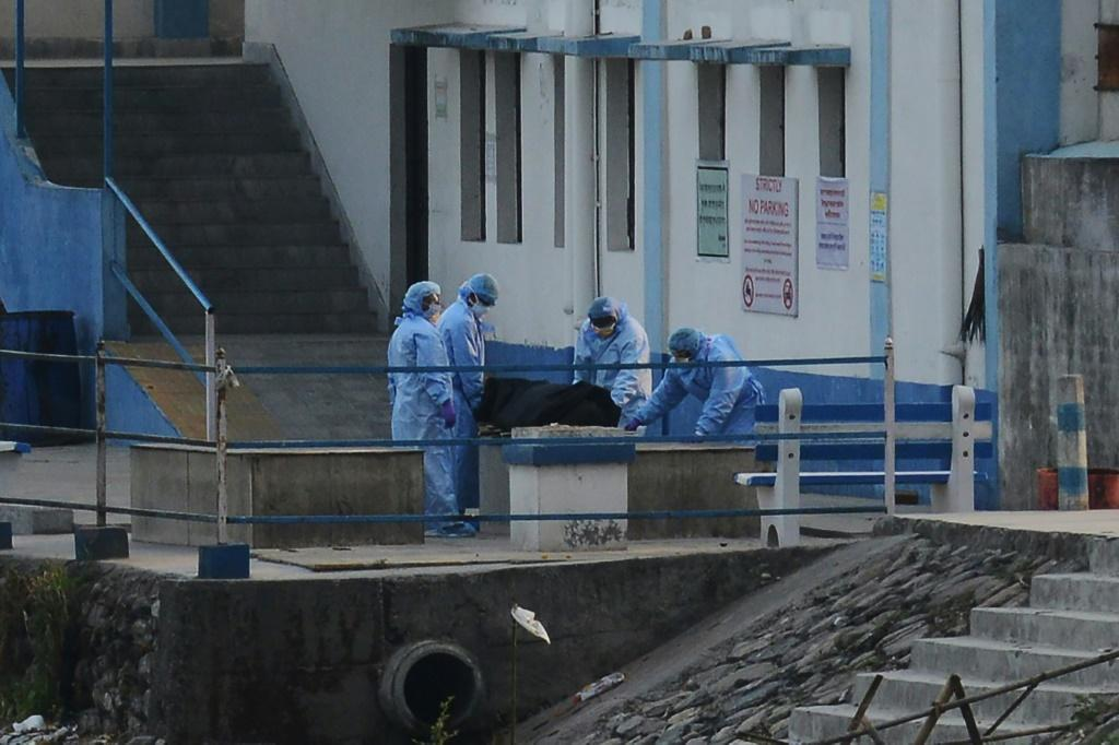 Staff wearing protective gear prepare to cremate a body at the North Bengal Medical College and Hospital in India