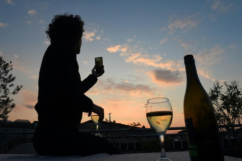 A French woman under lockdown raises a glass of wine