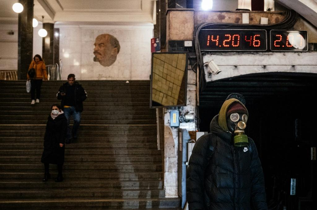 A man wearing a gas mask waits on the platform at the Biblioteka Imeni Lenina metro station in Moscow
