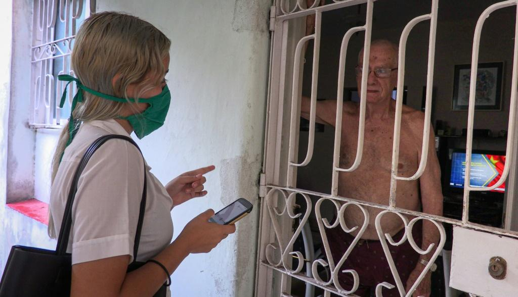 Cuban medical student Susana Diaz interviews a man as she searches for possible coronavirus cases