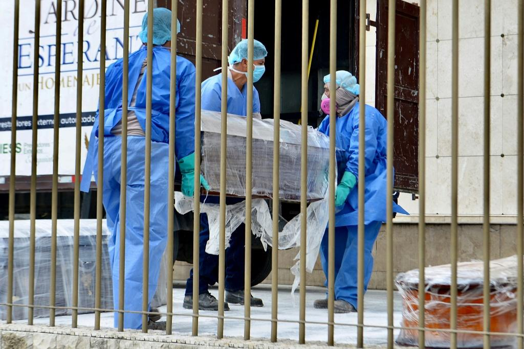 Employees wearing protective gear carry a coffin wrapped in plastic at a cemetery in Guayaquil on April 1