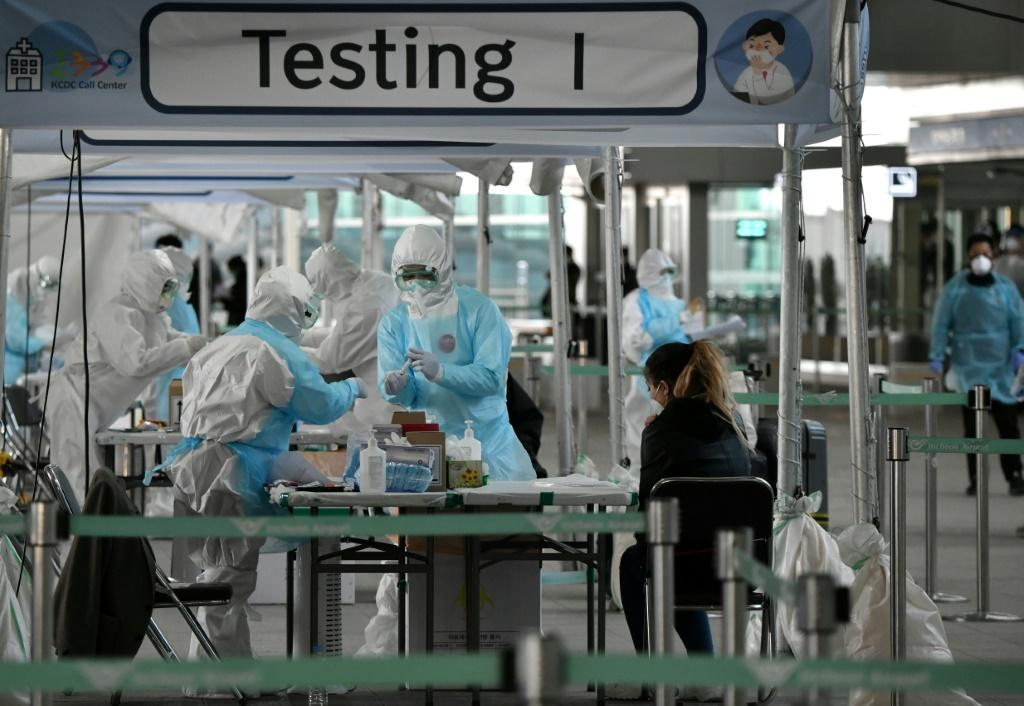 Medical staff wearing protective clothing take test samples for the COVID-19 coronavirus from a foreign passenger at a virus testing booth outside Incheon international airport near Seoul