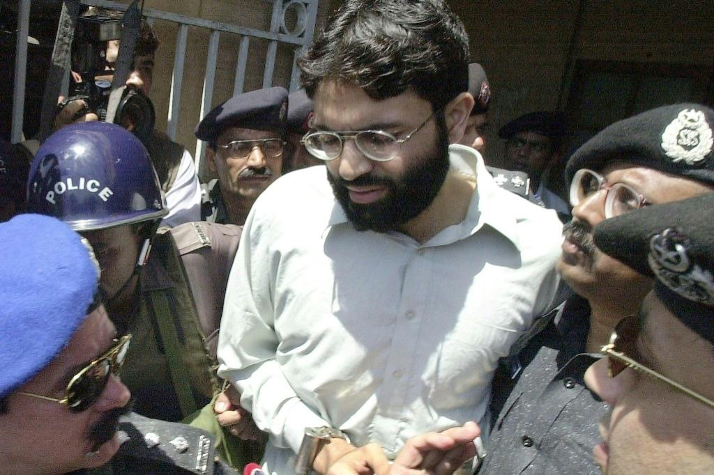 Pakistani police surround handcuffed Omar Sheikh in 2002 as he comes out of a court in Karachi