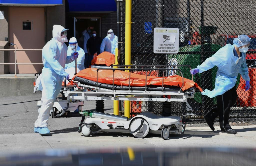 Medical staff move bodies from the Wyckoff Heights Medical Center to a refrigerated truck in Brooklyn, New York