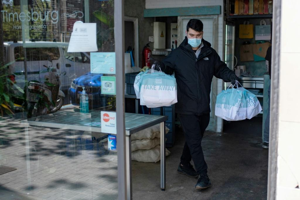 A delivery man leaves a restaurant with food for health workers in Barcelona