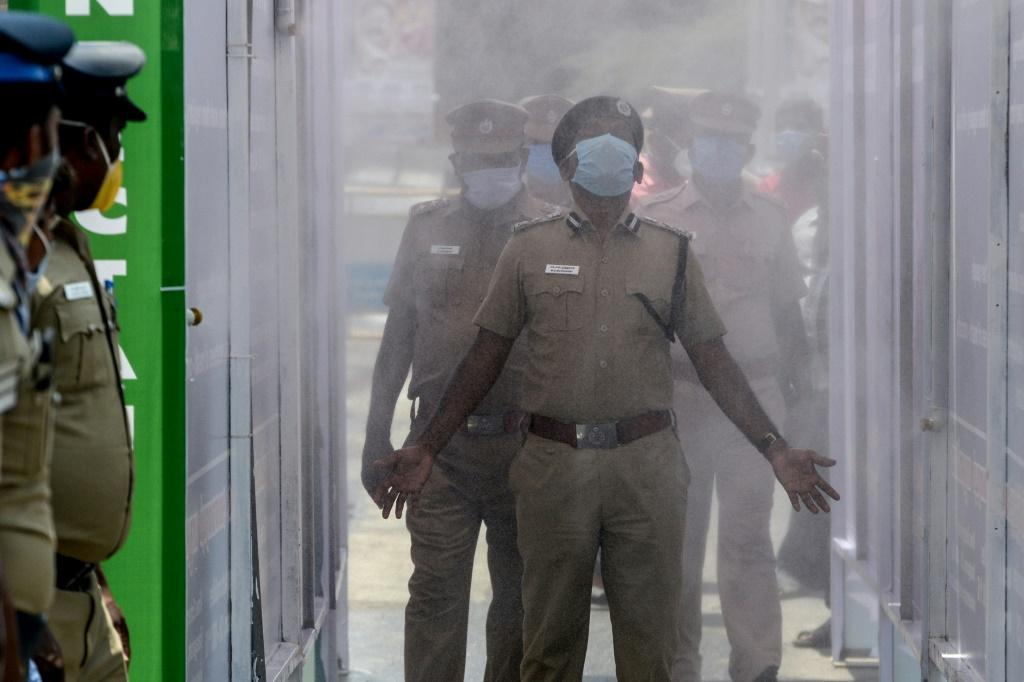 Indian police walk through a disinfection tunnel during a government-imposed nationwide lockdown