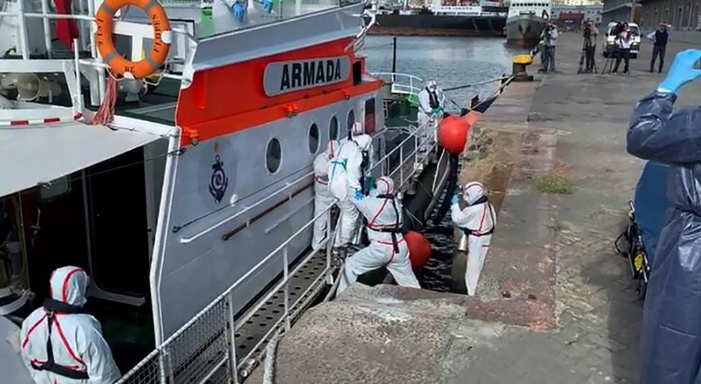 Medics help a sick passenger from an Australian liner off a Uruguay navy launch in Montevideo, on April 3, 2020