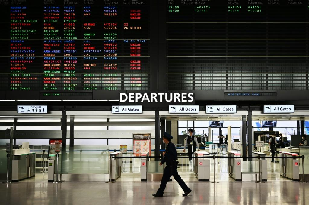 """A security guard walks past a signboard showing cancelled flights at the international departures area of Narita International Airport in Narita, Japan -- Prime Minister Shinzo Abe said the country's hospitals face a """"critical situation"""