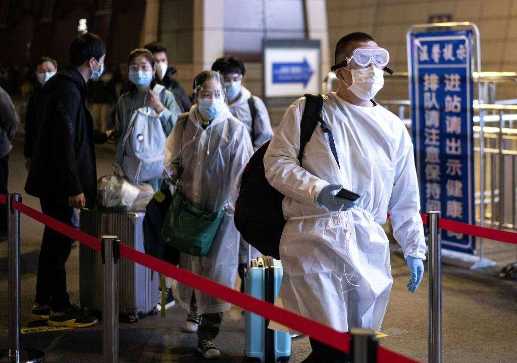 Passengers wear hazmat suit as they arrive at the Wuhan Wuchang Railway Station in leave the original epicenter of the COVID-19 coronavirus