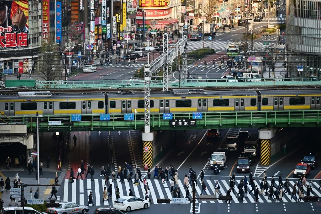 People cross a street in Tokyo on the same day Japan's Prime Minister Shinzo Abe declared a state of emergency in parts of the country, including Tokyo, over a spike in coronavirus infections