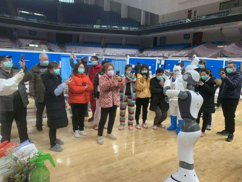 A handhout picture provided by CloudMinds shows Wuhan smart field hospital staff looking at an XR1 robot being deployed for coronavirus patient care