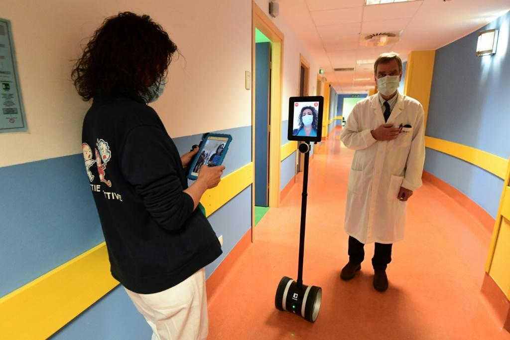 A nurse (L) manipulates a robot called Ivo used to help patients infected by the novel coronavirus at the Circolo di Varese hospital in Italy amid the the spread of the pandemic