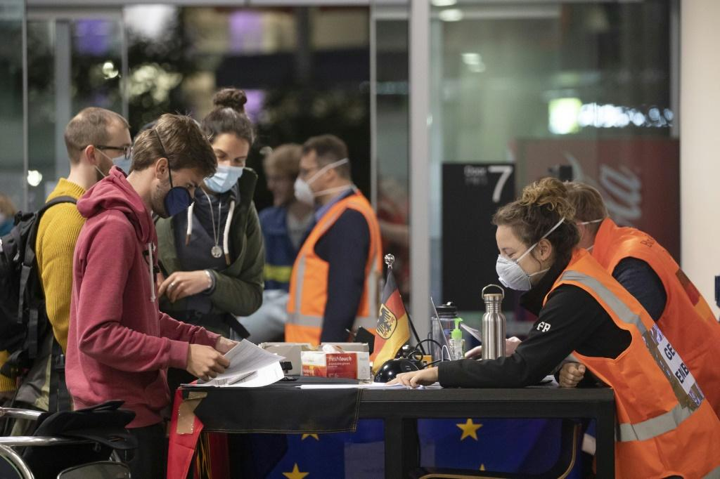 Embassy staff check documents ofGerman tourists as they prepare to check inbefore boarding a special flight for Frankfurt at Christchurch Airport in New Zealand