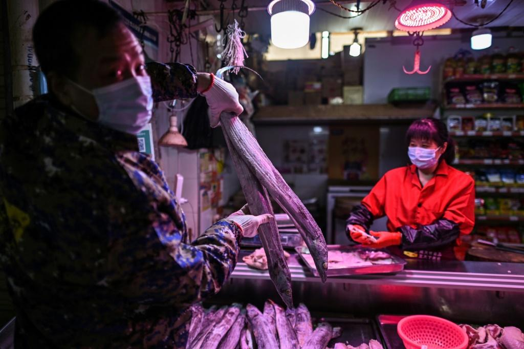 A man buys fish at a market stall in Wuhan, which is slowly returning to life after more than two months of near total lockdown