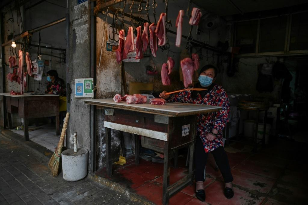 A woman tends her meat stall in Wuhan, where the coronavirus started. Life is slowly returning to normal in the city, but fears remain