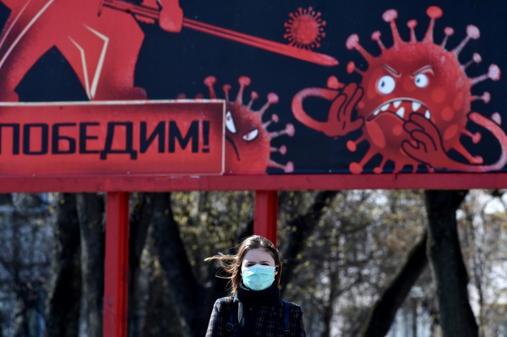 A woman wearing a face mask walks past a sign depicting a virus in Minsk