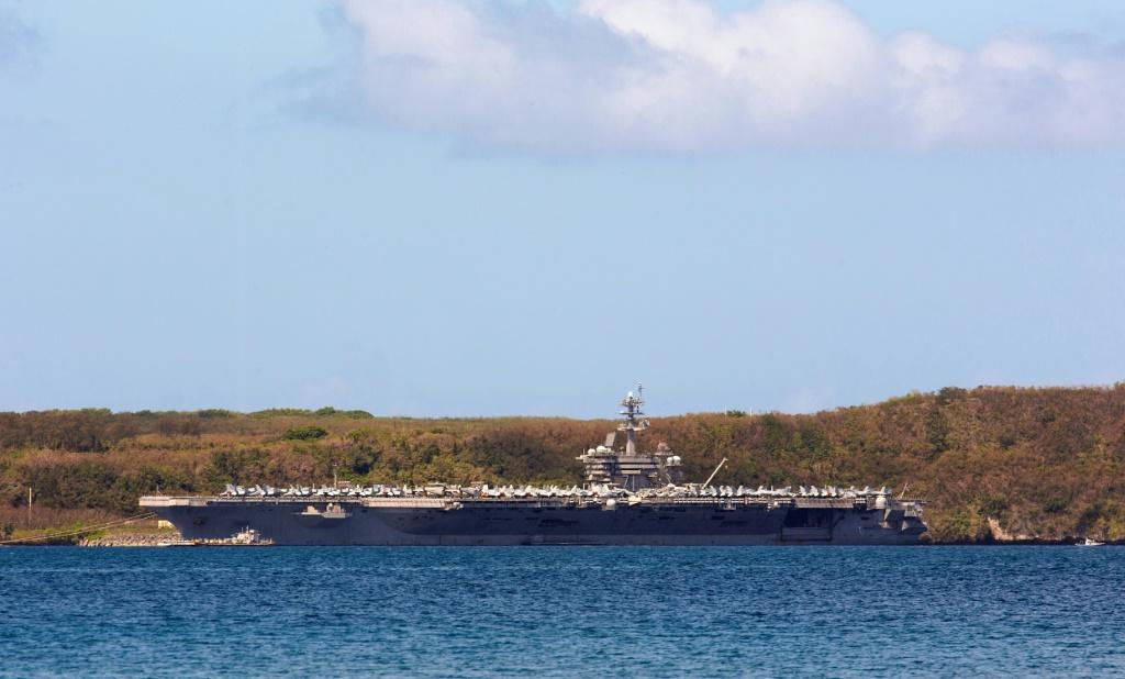 The aircraft carrier USS Theodore Roosevelt docked in Guam as authorities try to counter a coronavirus outbreak that has infected at least 585 of the ship's 4,800 crew and left one saiilor dead