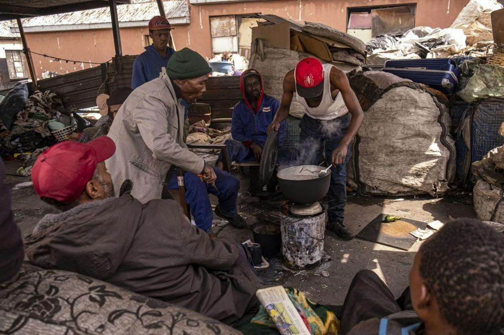 A group of reclaimers -- people who pick up and sell recyclable rubbish -- cook food at the Bekezela slum in Johannesburg. Most people here are depending on food donations to survive during the country's lockdown