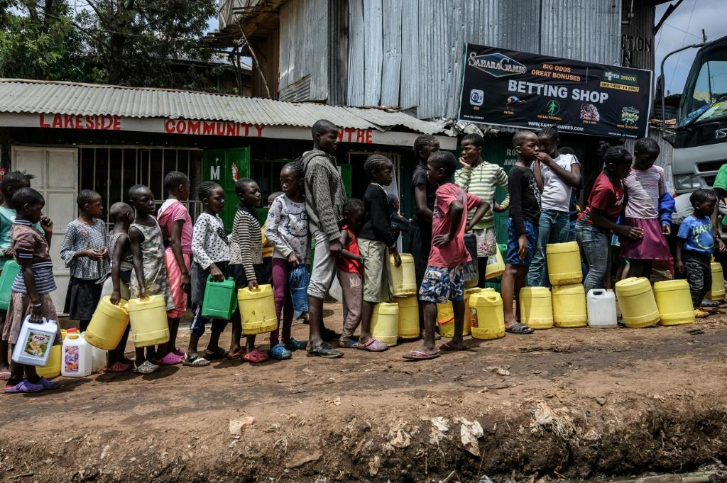 Children wait in line for water, distributed for free in the Nairobi slum of Kibera last week. Health experts say close queueing breaks the rule of social distancing to prevent virus infection