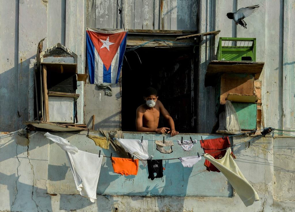 A man in a facemask stands on his balcony in Havana, Cuba