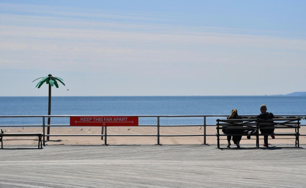 A sign reading 'Keep This Far Apart', remind speople of social distancing, is seen on the Coney Island boardwalk in New York City