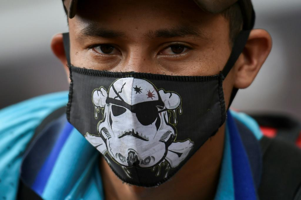 A Venezuelan migrant wears a face mask as he waits to board a bus to voluntarily return to his country because of the novel coronavirus in Cali, Colombia, on April 14