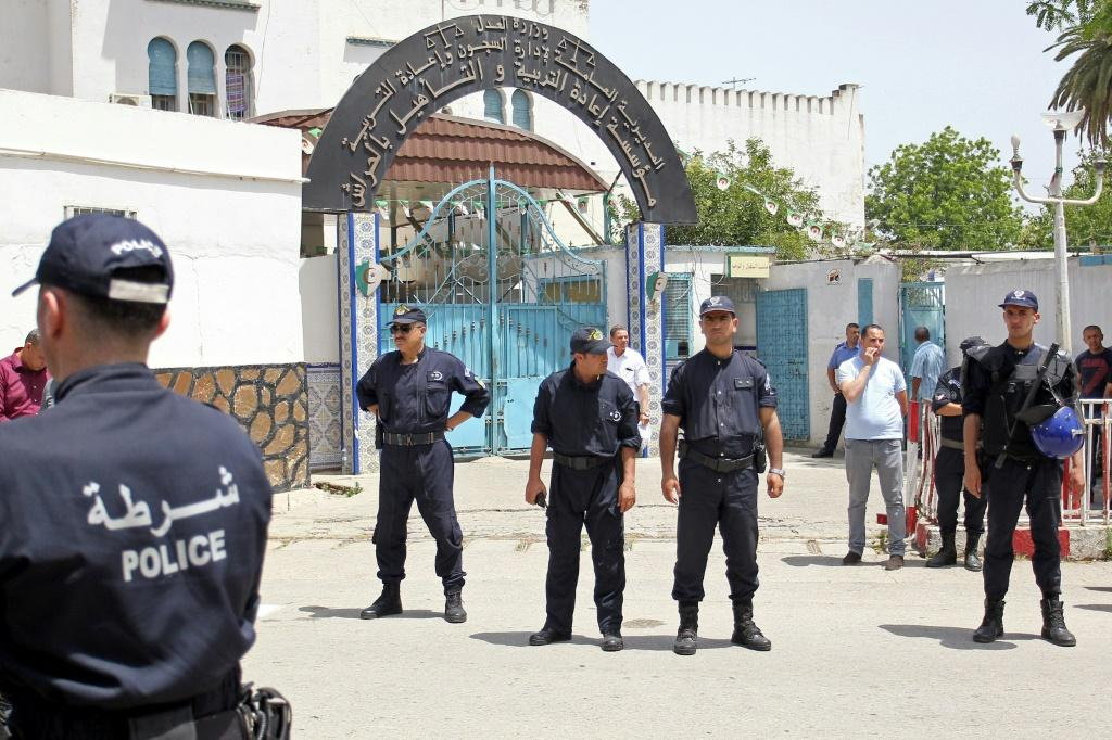 Algerian policemen stand outside the El Harrach prison in a suburb of the capital Algiers