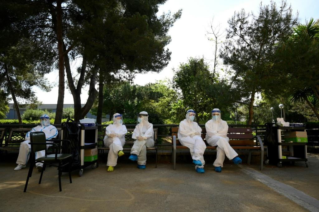 Healthcare workers wearing protective suits wait during a COVID-19 testing campaign at a care home for the elderly in Barcelona