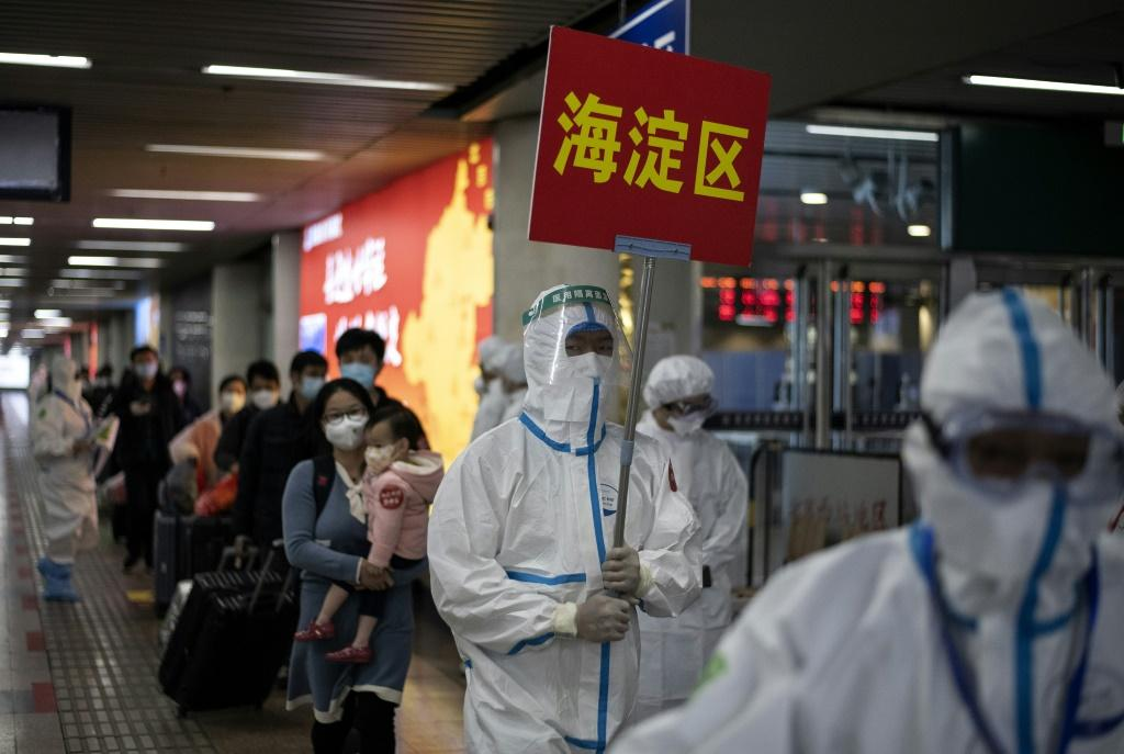 Transport personnel wearing hazmat suits guide travellers arriving from Wuhan to buses, which will take them to their quarantine locations, at Beijing West Railway Station