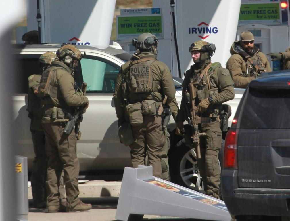 Members of a Royal Canadian Mounted Police tactical unit confer after a suspect in a deadly shooting rampage was neutralized at the Big Stop near Elmsdale, Nova Scotia