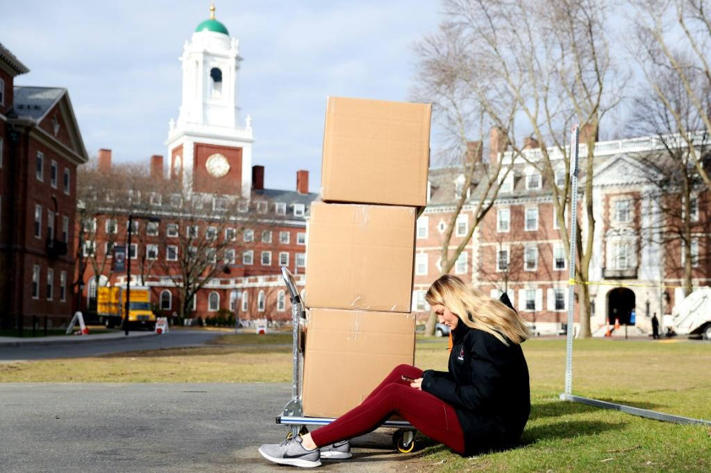 A Harvard student sits with her belongings before returning home on March 12, 2020, as students left campus due to the coronavirus pandemic