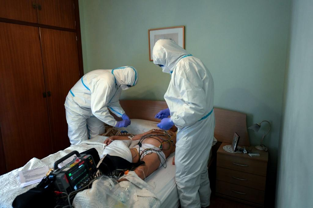 Health care workers in Madrid wearing protective suits examine a man who has fallen ill at home -- Spain is one of the countries worst hit by the coronavirus crisis