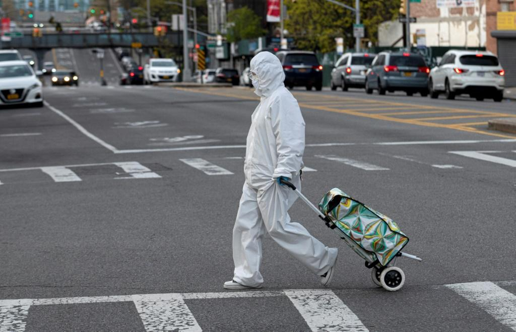 A woman wearing a hazmat suit and googles pulls her grocery cart through New York City on April 20, 2020