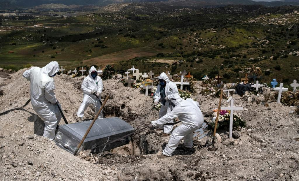 Cementery workers wearing protective gear bury an unclaimed COVID-19 victim, at the Municipal cementery No. 13 in Tijuana, Baja California state, Mexico