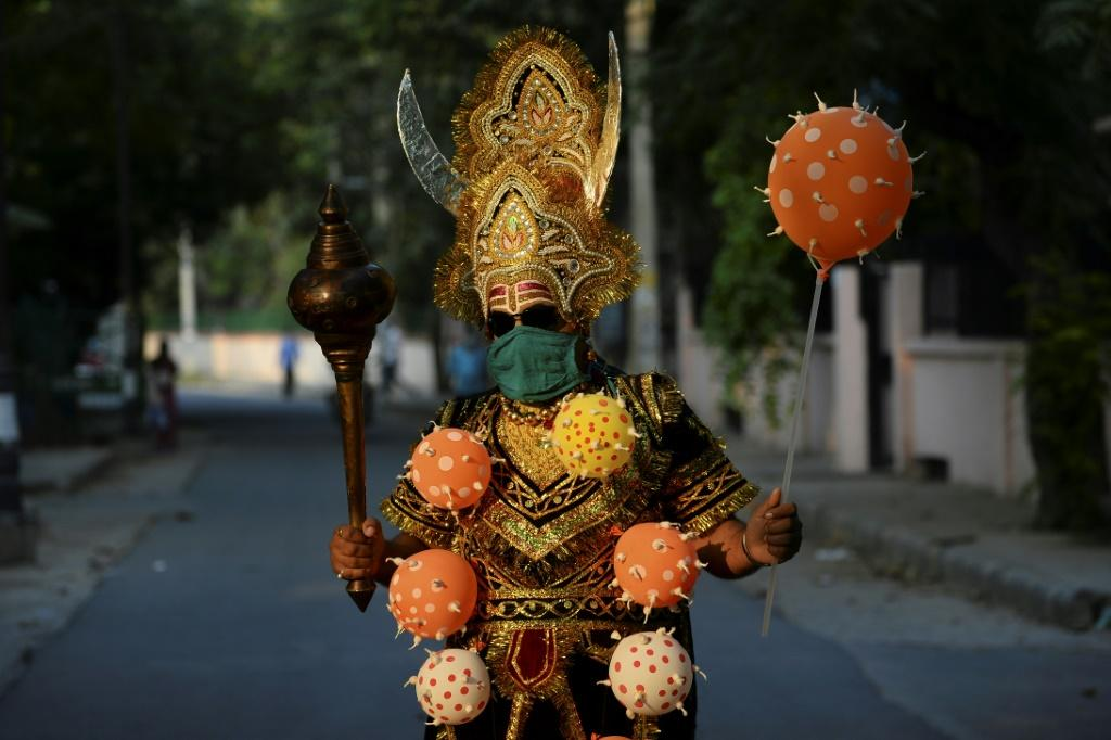 A man dressed as 'Yamraj', the Hindu mythical angel of death, campaigns to raise awareness on the importance to stay home and maintain social distancing during an event organised by Delhi police