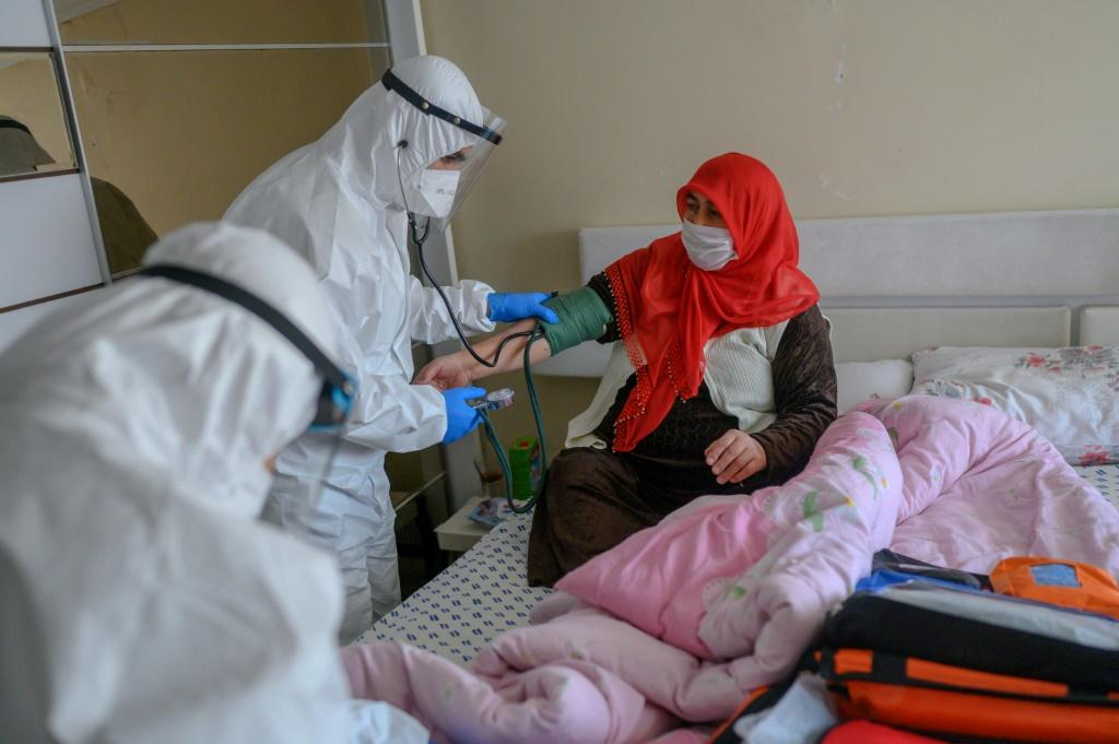 Health workers help a woman who tested positive for the novel coronavirus COVID-19, at Bagcilar in Istanbul