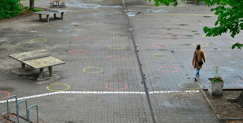 A woman walks in the schoolyard of an elementary school in Berlin where circles have been painted on the ground to mark the recommended distance, in preparation of the return of some pupils from early May 2020